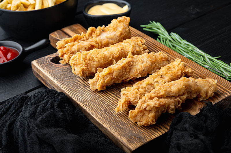 Crispy chicken tenders on black wooden background